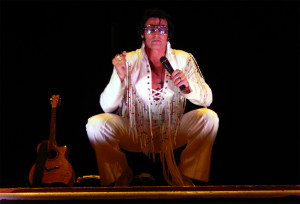 Billy Lindsay, Elvis Presley impersonator stooping down on stage at the Borini Theater in Kings Point Sun City Center, FL