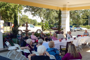 Residents at car show party under portico at Cypress Assisted Living Residence in Sun City Center, Florida