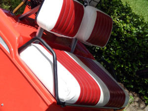 Customized red and white seats in 1957 Chevy Bel-Air Club Car golf cart next to Kings Point Security Entrance in Sun City Center, FL