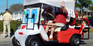 ED BARNS waving to crowd in Sun City Center Holiday Golf Cart Parade 2013