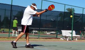 John Marinchek hitting ball in 75+ Mens Doubles Pickleball in Tampa Bay Senior Games, Sun City Center, FL [DAY ONE: Friday, October 25, 2013]