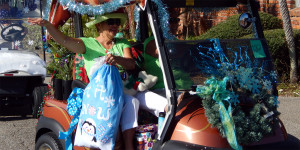 Lady in golf cart holding bag that reads 'Let it Snow' (#182) at beginning of Sun City Center Holiday Golf Cart Parade 2013