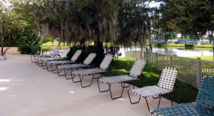 Main Clubhouse Pool with lounge chairs at edge of in Kings Point, Sun City Center, FL