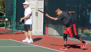 Man serving ball in Pickleball Doubles at Tampa Bay Senior Games, Sun City Center, Florida [DAY ONE: Friday, October 25, 2013]
