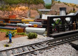 Man standing on train bridge at the Sun CIty Center Model Railroad Club