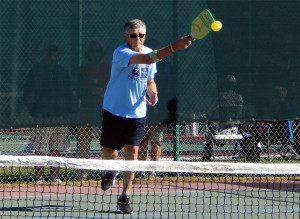 Man hits ball in Pickleball Doubles tournament at Tampa Bay Senior Games 2013, Sun City Center, Florida [DAY ONE: Friday, October 25, 2013]