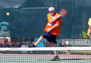 Player hitting ball on one foot in Mixed Doubles Pickleball Tournament 2013 Tampa Bay Senior Games, Sun City Center [DAY THREE: Sunday, October 27, 2013]