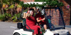 Woman ringing Christmas bells in golf cart in Sun City Center Holiday Golf Cart Parade 2013