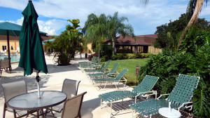 Main Clubhouse Pool with umbrellas, lounge chairs on deck in Kings Point, Sun City Center, FL