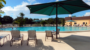 Main Clubhouse Pool with tables and chairs on pool deck in Kings Point, Sun City Center, FL