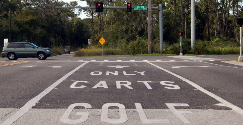Golf Cart Lane Only stensiled on Cape Stone Ave for 301 golf cart crossing leaving Walmart
