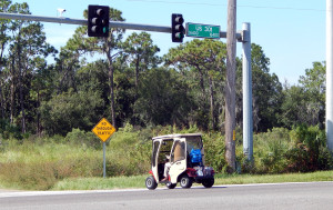 Golf cart crossing over 301 while leaving Walmart heading to golf cart path