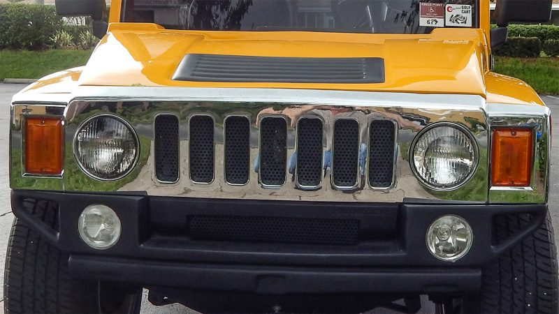 Front grille and hood of Hummer H3 yellow golf cart