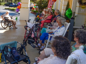 Residents at High Rollers Car Club Show in shade under portico at Cypress Assisted Living Residence in Sun City Center, Florida