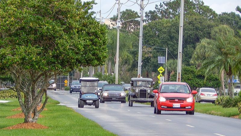 Classic cars, news cars, golf carts sharing the same road in Sun City Center, FL