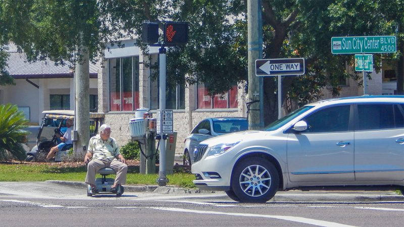 Man in wheel chair/scooter waiting to cross S.R, 674 on electric wheel chair/scooter  in Sun City Center, FL