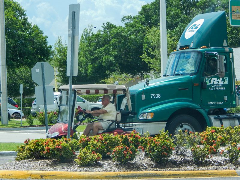A golf cart pulls ahead of tractor trailer when light turned green  on North Pebble Beach Blvd and S.R. 674