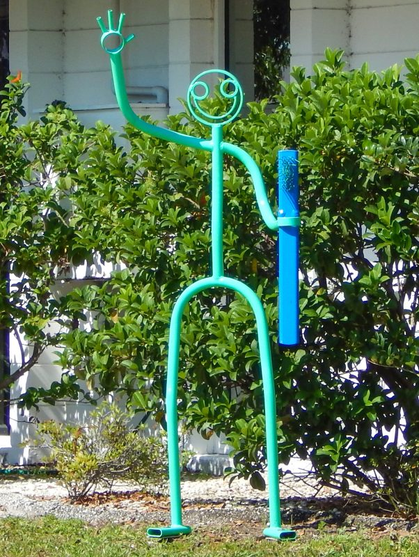 SCRUBS & CLOGS Store with green stickman art sculpture out front holding a blue scrub brush in Sun City Center, FL