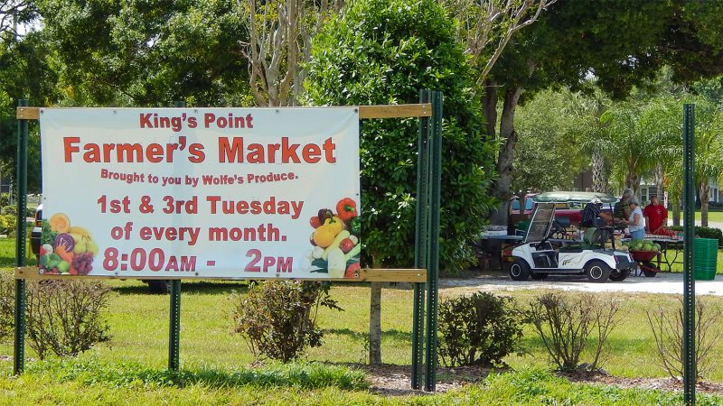 Road sign on SR 674 for Kings Point Farmers Market by Wolfes Produce