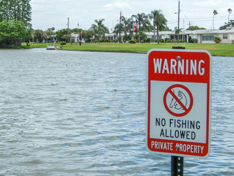 WARNING sign reads 'No Fishing Allowed and Private Property' at Swan Lake in Sun City Center, FL