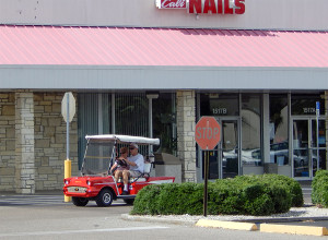 57 Chevy Bel Air golf cart driving by Cali Nails in Sun City Center Plaza