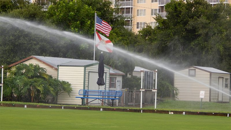 July 20, 2014 - high pressure spinkler sprays lawn bowling field with flags in background in Kings Point