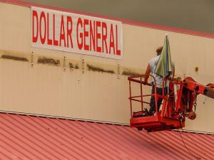 July 8, 2014: Man in G85 Elliott Lift by roof of Dollar General in Sun City Center Plaza