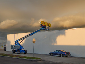 July 8, 2014: Two men on lift raising GENERAL sign to roof of Dollar General in Sun City Center Plaza