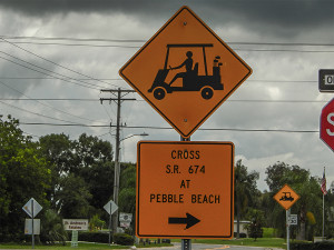 Yellow sign for golf carts on El Rancho Dr reads 'Cross S.R. 674 at Pebble Beach'