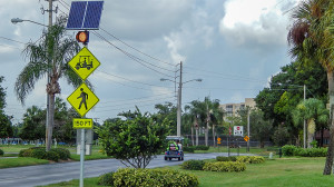 A flashing yellow light warns to watch out for golf carts and pedestrians for the next 150 feet on Kings Blvd heading towards gate