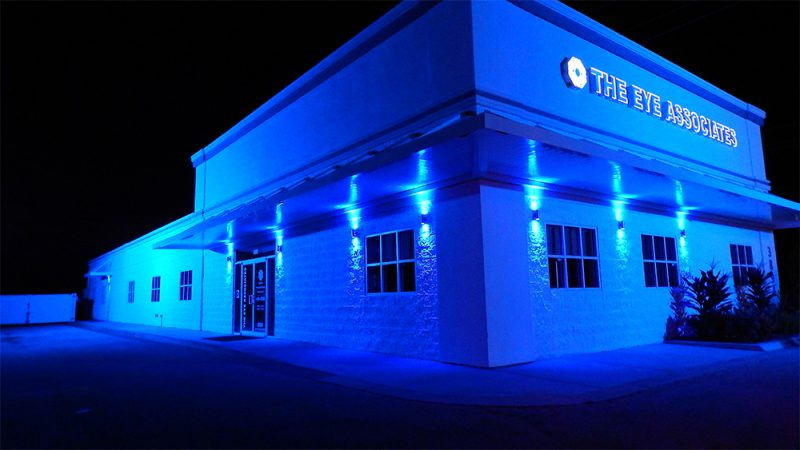 The Eye Associates building at night illuminated with blue lights in Sun City Center, FL.